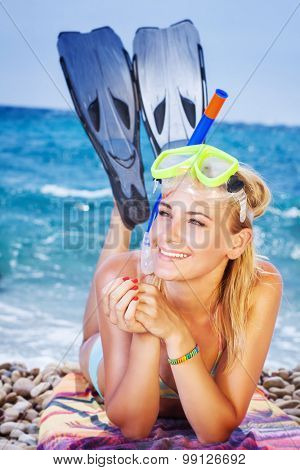 Happy woman on the beach, wearing snorkeling equipment lying down on the seashore, pretty girl is interested in water sports, active summer vacation