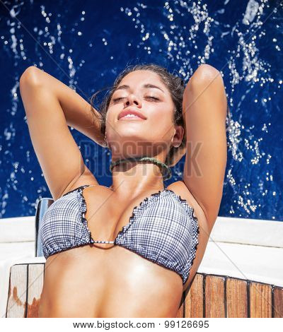 Beautiful woman tanning on the sailboat, lying down on the deck and with closed eyes enjoying summer vacation among the sea