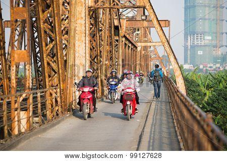 People ride motorbike in Long Bien bridge in Hanoi, Vietnam.