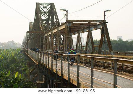 People ride motorbike in Long Bien bridge in Hanoi, Vietnam