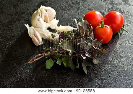 bunch of basil, tomatoes and garlic on black table
