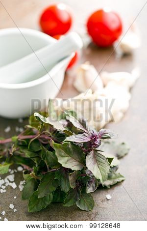 bunch of basil and tomatoes on kitchen table