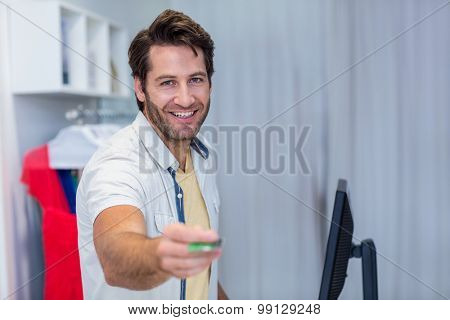 Portrait of smiling cashier handing back credit card in clothing store