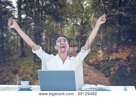 Businesswoman celebrating a great success against scenic view of walkway along lush forest