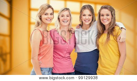 Four friends standing beside each other and smiling against room with large window showing city