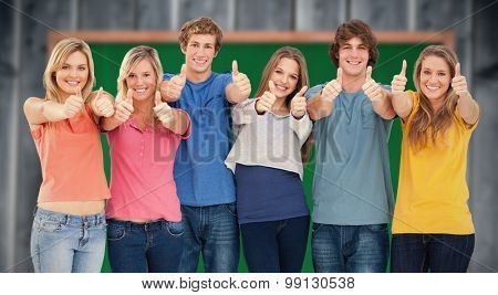 Six friends giving thumbs up as they smile against blackboard with copy space on wooden board