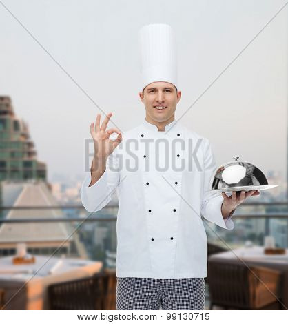 cooking, profession, gesture and people concept - happy male chef cook holding cloche and showing ok sign over city restaurant lounge background