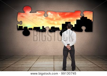 Businessman turning his back to camera against cityscape stencil on red sky
