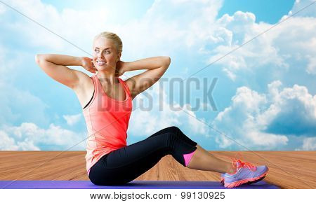 fitness, sport, exercising and people concept - smiling woman doing sit-up on mat over wooden floor and sky with white clouds background