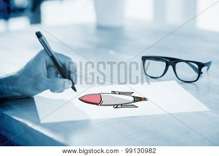 Side view of hand writing on white page on working desk against rocket