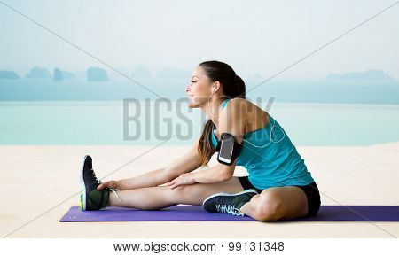 fitness, sport, training, technology and people concept - smiling woman with smartphone and earphones listening to music and stretching leg on exercise mat over sea and pool at hotel resort background