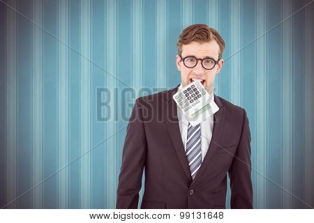Geeky businessman biting calculator against background