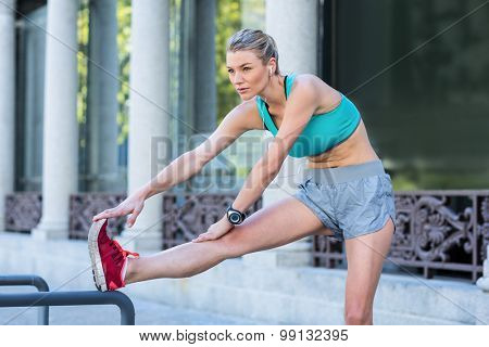 A beautiful woman stretching her leg on a sunny day