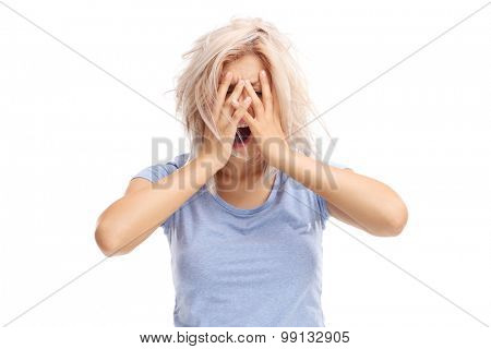 Desperate young woman holding her hands on her head isolated on white background