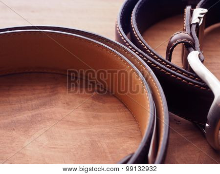 Two quality leather belts on a rustic wooden table. Shallow depth of field.