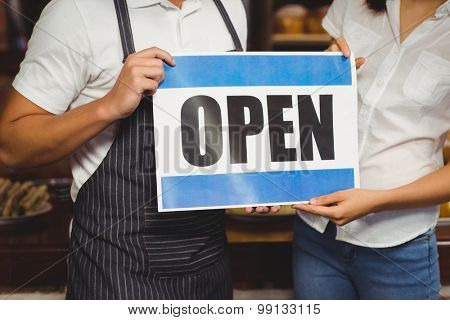 Close up view of waiter and waitress posing with open sign