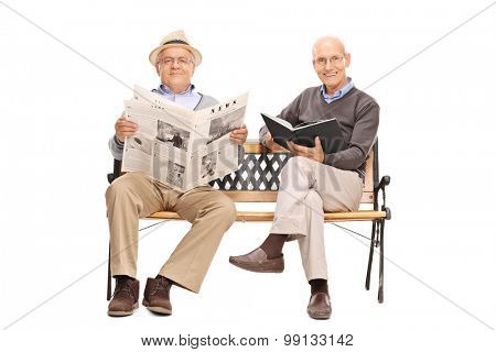 Two senior gentlemen sitting on a bench and holding a book and a newspaper isolated on white background
