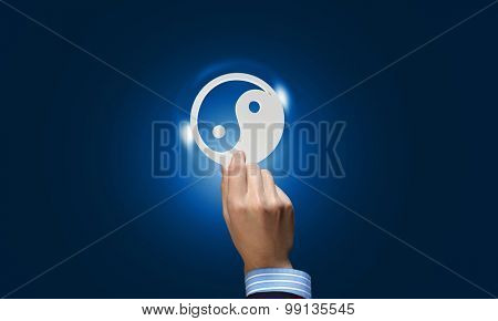 Close up of human hand with yin yang concept icon