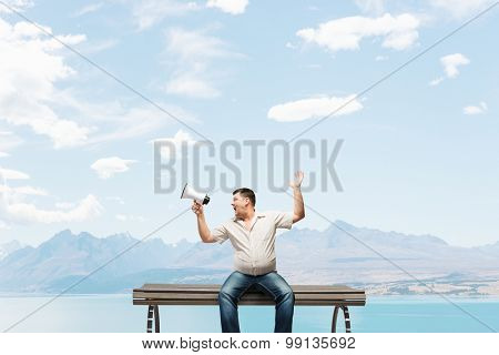 Fat man sitting on bench and screaming in megaphone