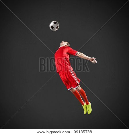 Soccer player kicking ball isolated over dark background