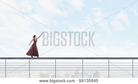 Woman in evening dress and blindfold walking on parapet