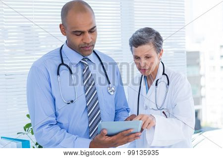 Concentrated medical colleagues with tablet computer in the hospital