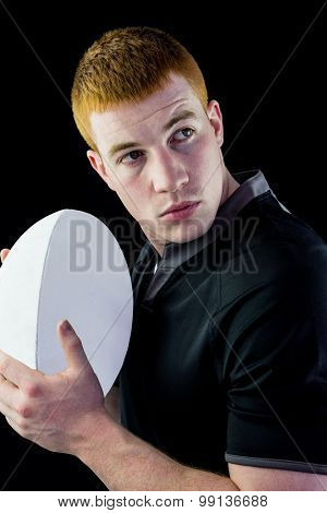 Profile view of a rugby player holding a rugby ball