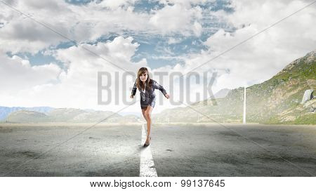 Young determined businesswoman standing in start position
