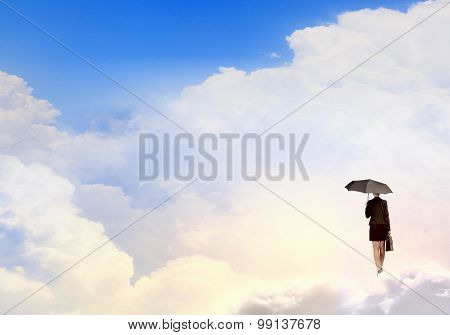 Young businesswoman with black umbrella standing on cloud