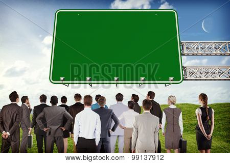 Business team against green road sign by road