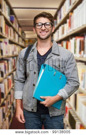 Student smiling at camera in library against close up of a bookshelf