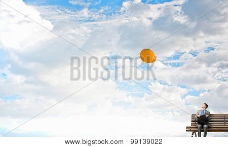 Young smiling businessman sitting on bench with briefcase in hands and looking at balloon in sky