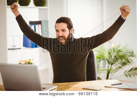 Hipster businessman cheering at his desk in his office