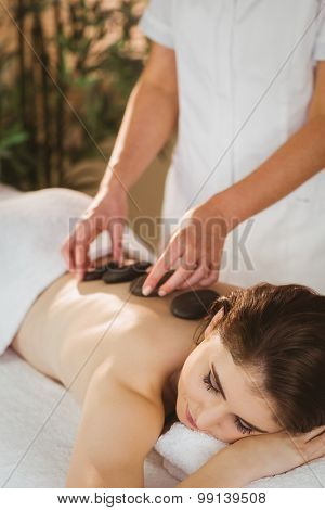 Young woman getting a hot stone massage in therapy room