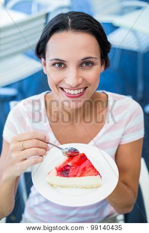 Smiling brunette taking a piece of chocolate cake at the cafe