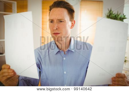 Serious businessman holding two paper sheets in his office