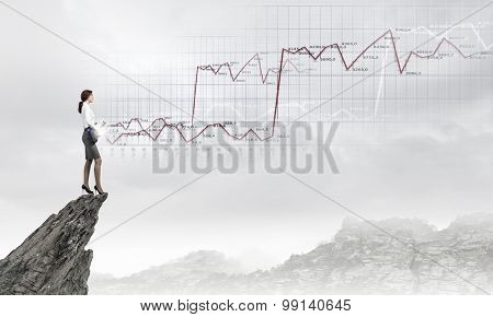 Cheerful businesswoman standing on rock edge and playing electric guitar