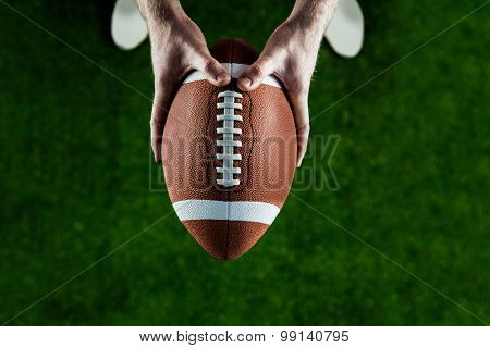 American football player holding up football on american football field