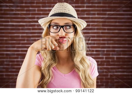 A beautiful hipster having a fake mustache against a brick wall