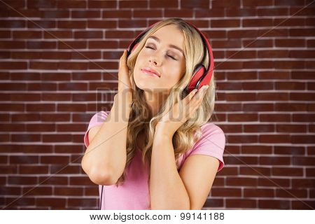 Pretty young woman with headphones against a red brick wall