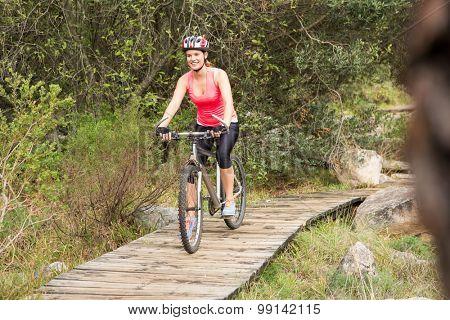 Smiling blonde athlete mountain biking in the nature