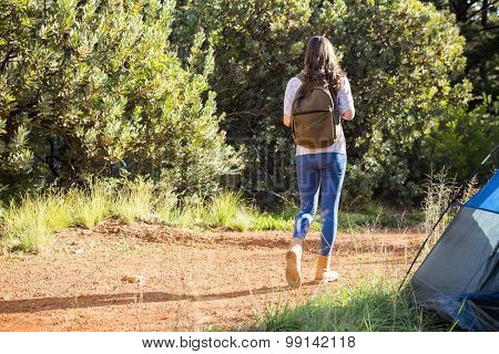 Brunette camper walking away from tent in the nature