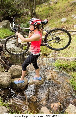 Blonde athlete carrying her mountain bike over stream in the nature
