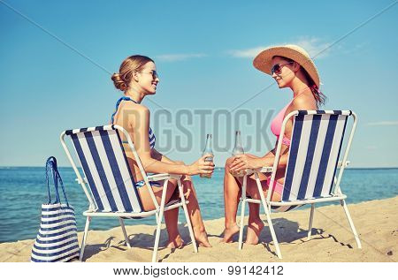summer vacation, travel and people concept - happy women drinking beer and sunbathing in lounges on beach