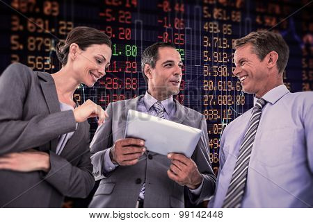Businessman showing tablet to his colleagues against stocks and shares