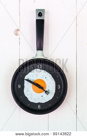 clock like a pan with fried egg on the wooden background