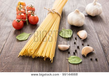 Pasta And Tomatoes With Herbs On Vintage Wooden Table