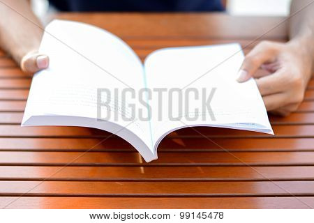 Hands Opening Book On The Table - Reading Concept