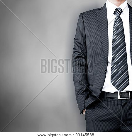 Businessman Wearing Suit & Tie Standing On Gray Background