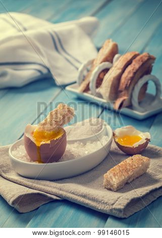 Buttered toast being dipped into soft boiled egg - focus on dipped toast slice